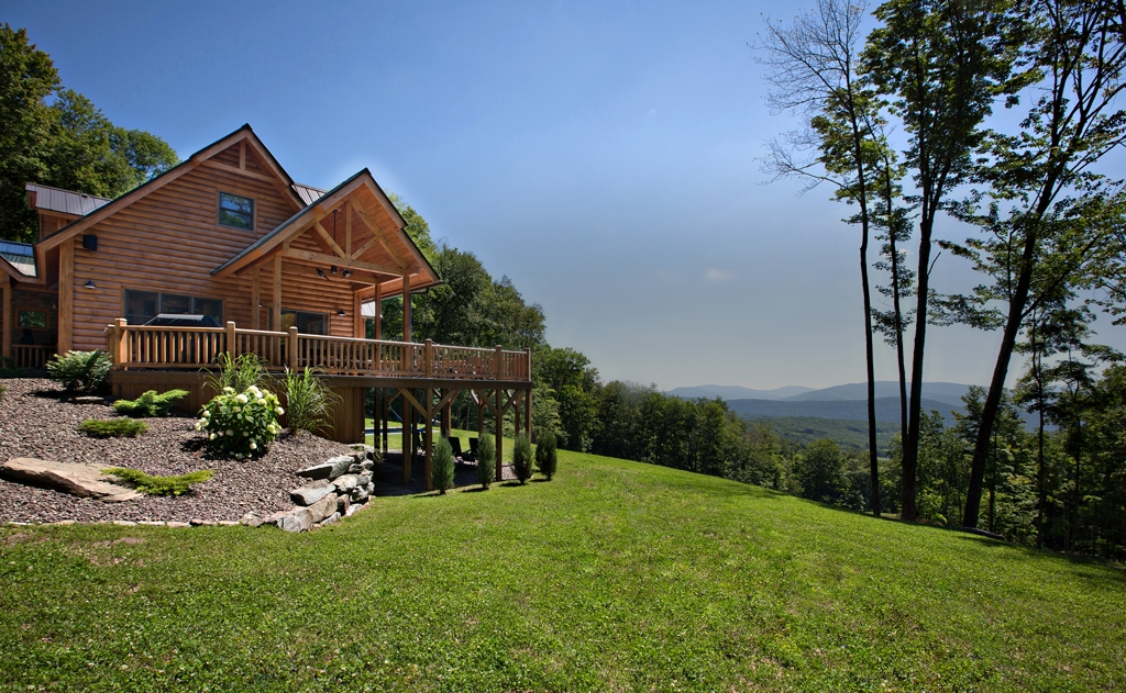 Log Home Stained with WOODguard Overlooking Hill
